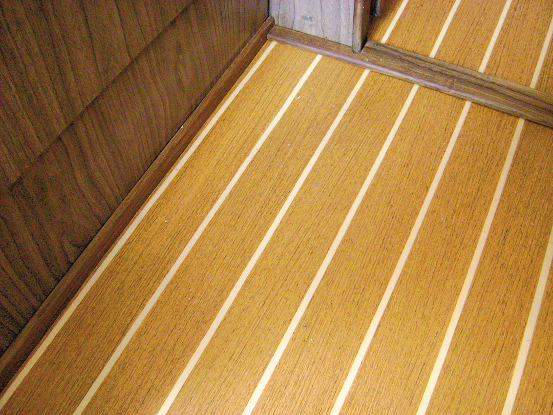 teak trim between vinyl flooring