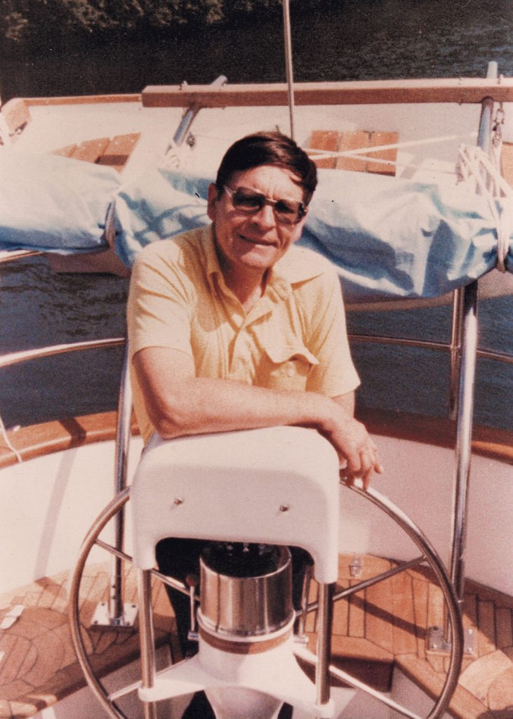 Ted Brewer at helm of sailboat