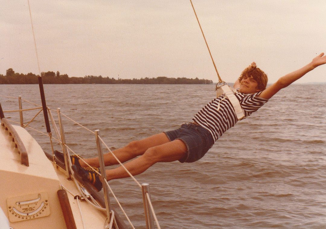 a teenager using a swing while on their sailboat